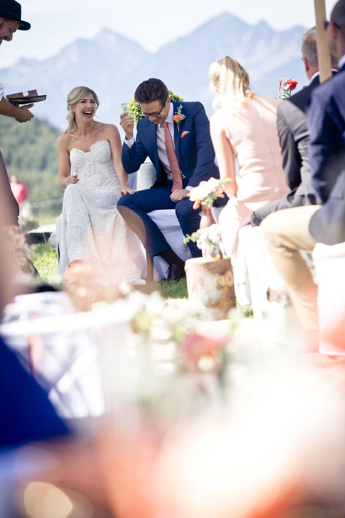 Braut und Bräutigam lachen während der Trauzeremonie