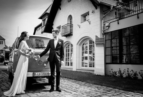 Braut und Bräutigam kommen im VW Bus zus Hochzeitsfeier