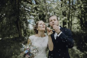 Brautpaar bläst Seifenblasen nach der freien Trauung im Wald