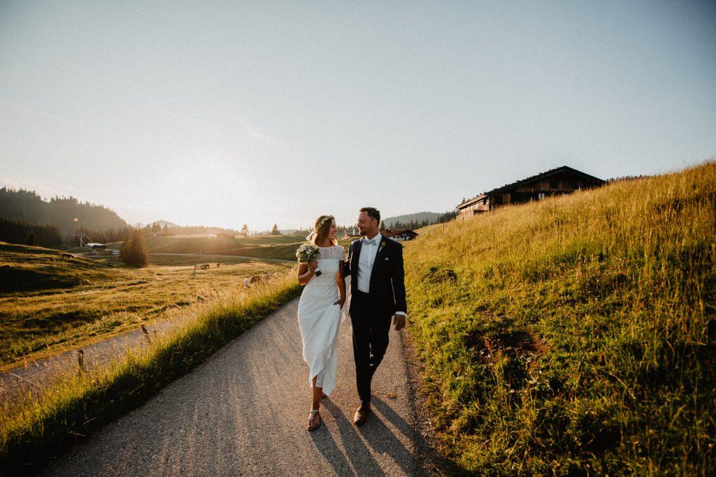 Brautpaar flaniert in den Bergen bei Sonnenuntergang