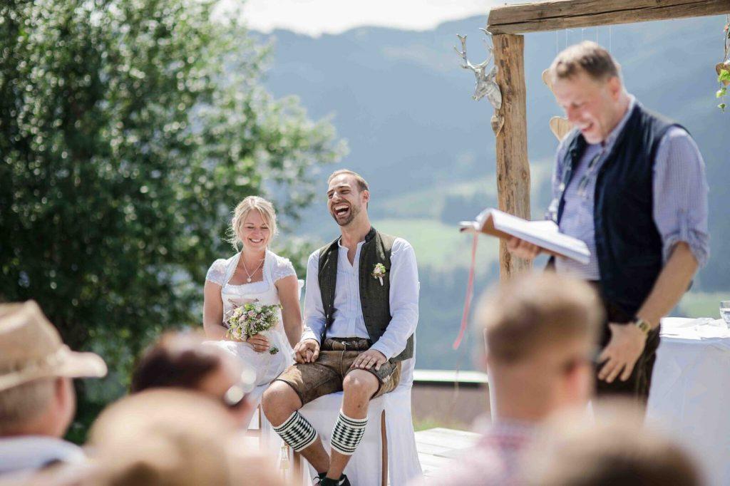 Lachendes Brautpaar in bayerischer Tracht bei seinen freien Trauung