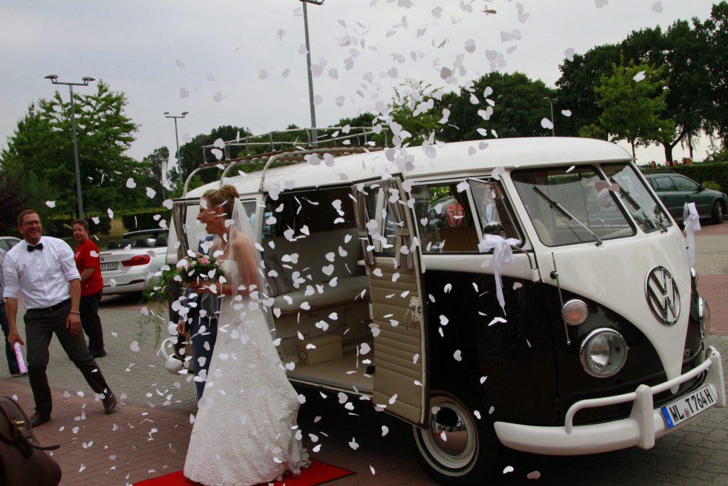 Braut bei der Ankunft für die freie Trauung in einer Wolke aus Blütenblätter