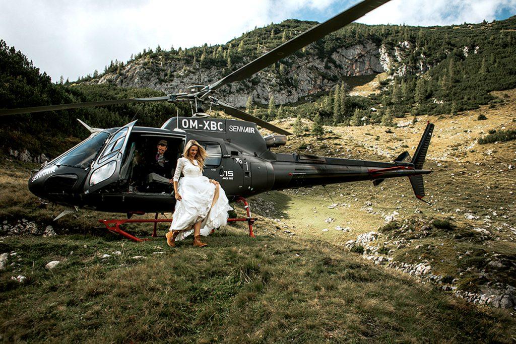Braut steigt aus einem Helikopter in den Bergen für ihre Hochzeit