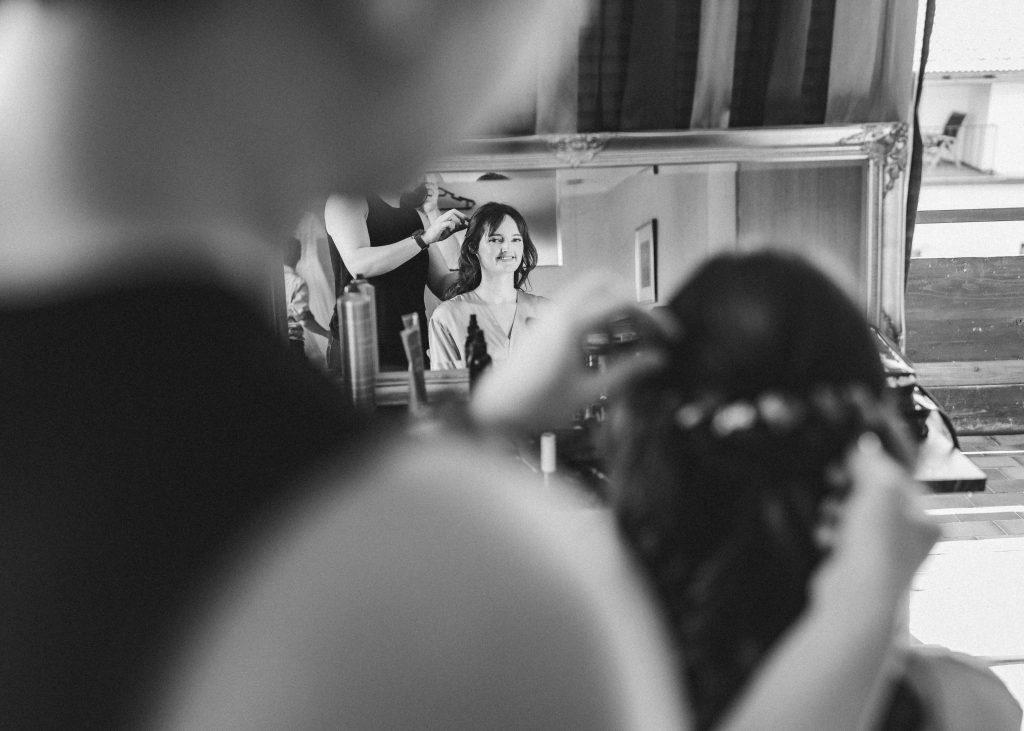 Braut wird geschminkt und frisiert für die Hochzeit