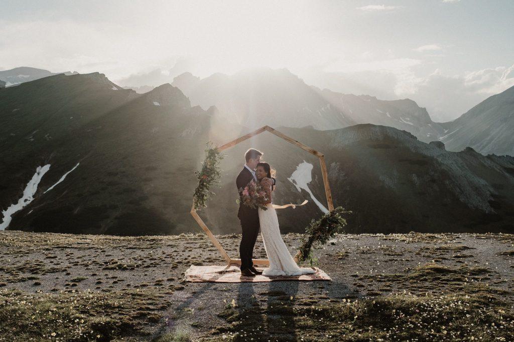 Brautpaar auf Bergspitze bei Sonnenuntergang