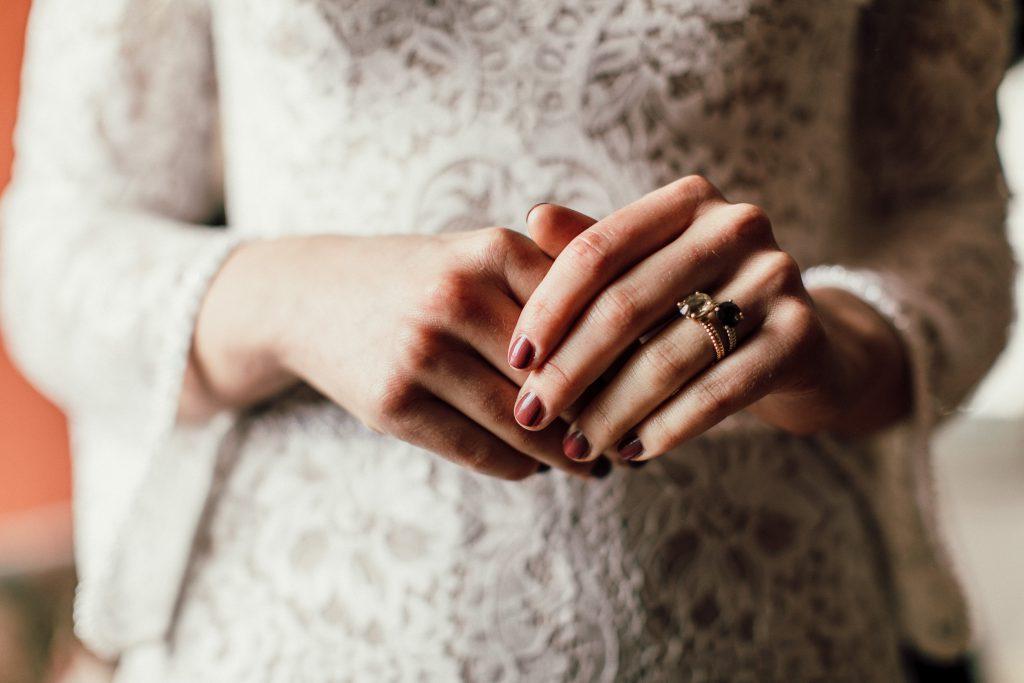 Großaufnahme Hände der Braut mit Verlobungs- und Ehering