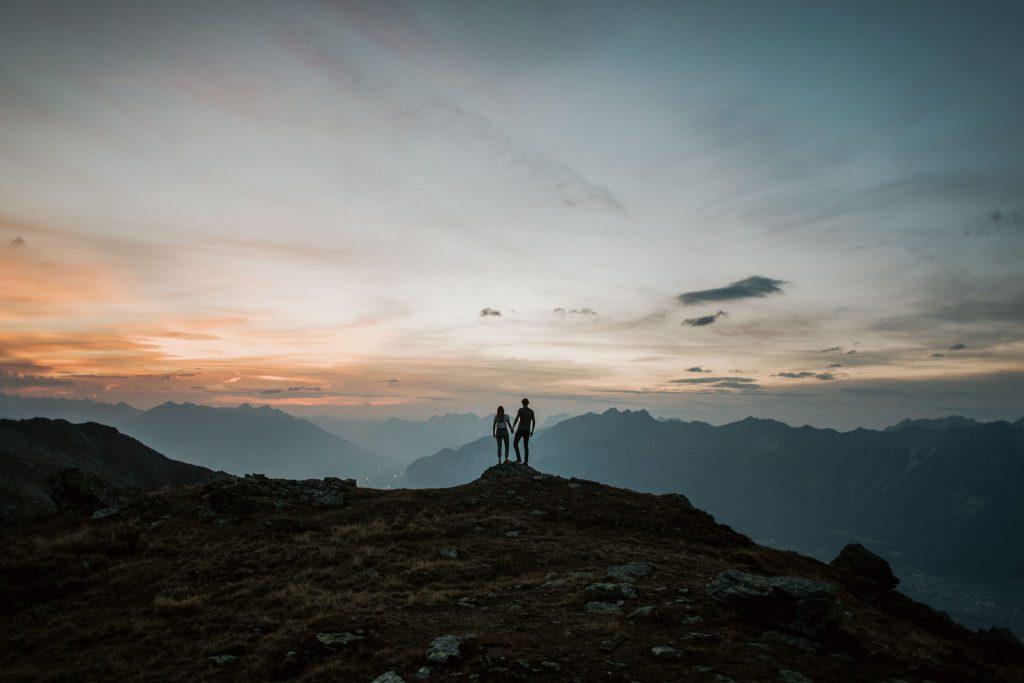 Paar auf Bergspitze vor Panorama im Sonnenuntergang