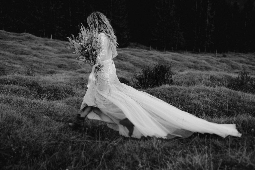 Strahlende Boho Braut bei der Hochzeit auf einer Almwiese