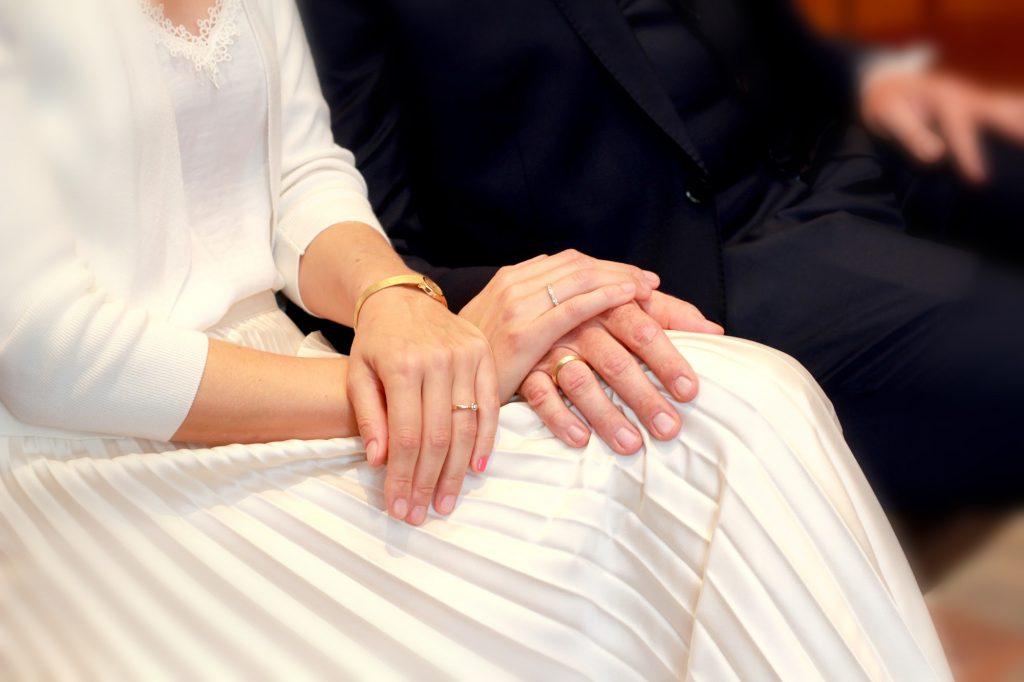 Die Hände eines Hochzeitspaares auf dem Standesamt