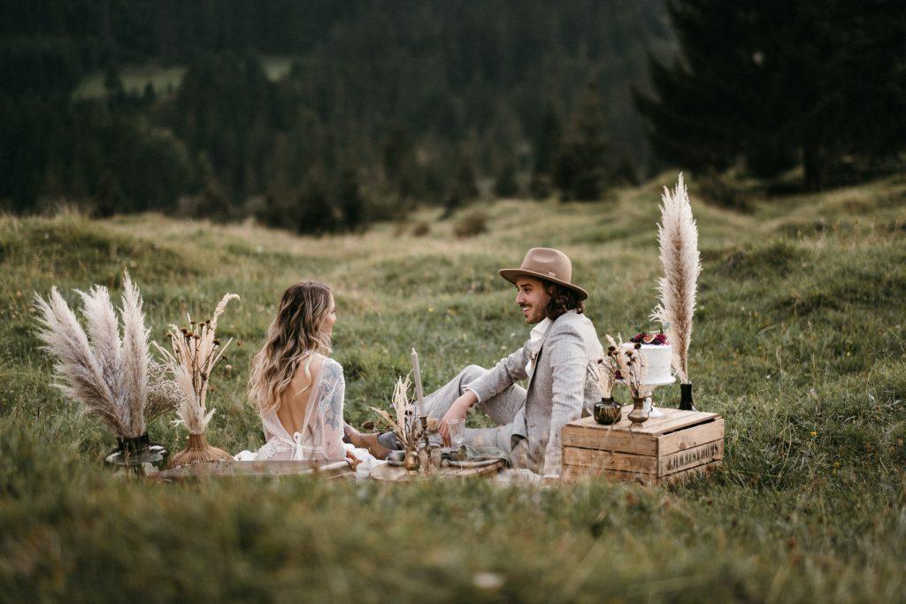 Elopement Brautpaar unter Blumenbogen beim Picknick auf einer Wiese