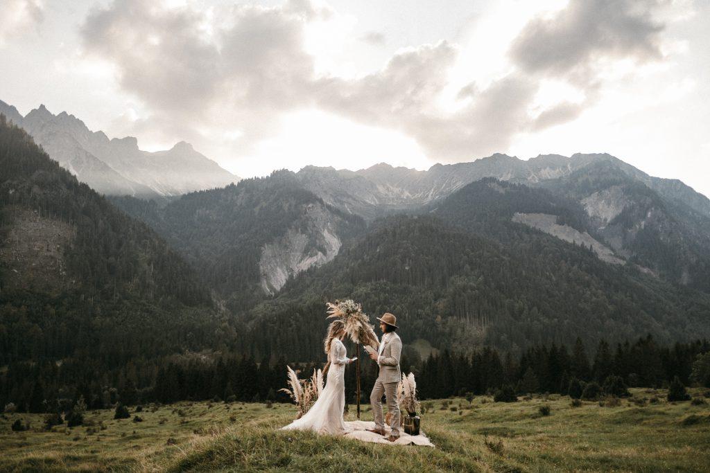 Elopement Brautpaar unter Blumenbogen auf einer Wiese mit Bergpanorama