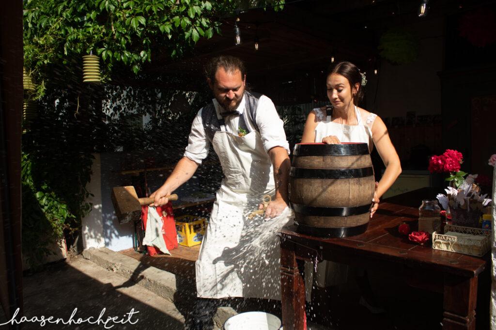 Brautpaar beim Anstich des Bierfasses während der Hochzeitsfeier
