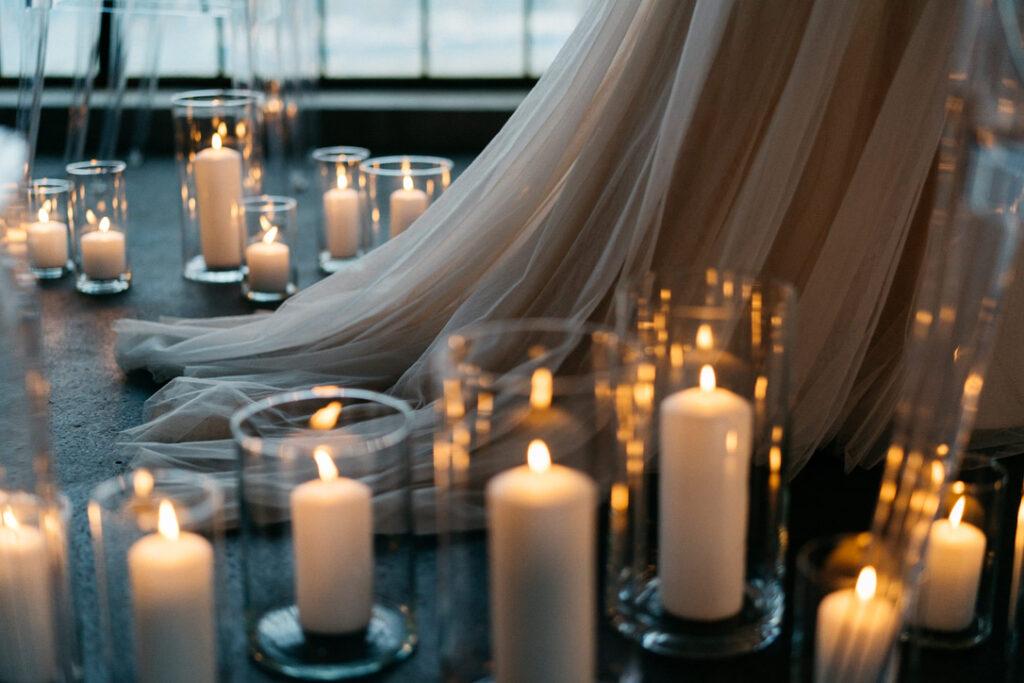 Die Schleppe einer Braut beim Einzug zwischen Kerzen