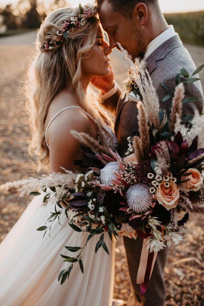 Brautpaar umarmt sich zärtlich auf einer Almwiese